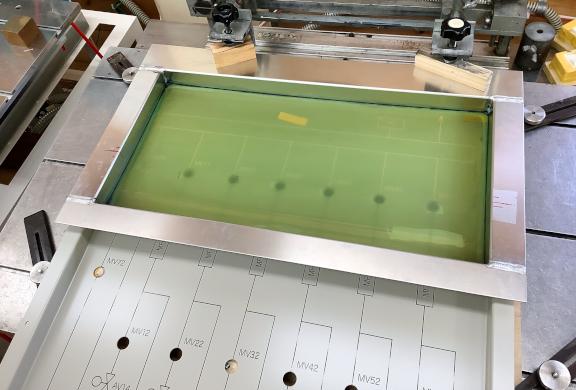 四辺立ち上がりのある形状ワークへの特枠印刷。大型のワークへ特枠がセットされた写真